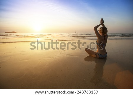 Beautiful girl sit at the seaside and meditating in yoga pose during amazing sunset.