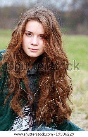 Beautiful girl sits in an autumn park