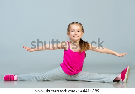 beautiful girl sits on a splits - stock photo