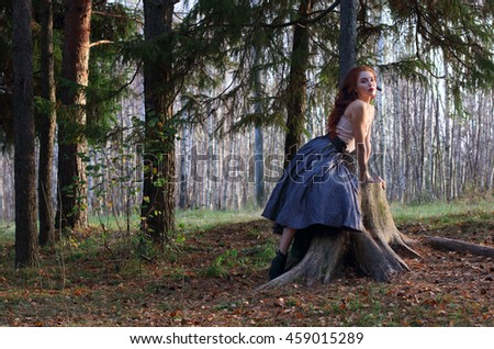 Beautiful girl sits on big stump and poses on wind in autumn forest