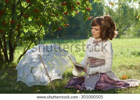 Beautiful girl sits on the lawn of the summer park under rowan tree and reads interesting book. There is a white sun umbrella beside her. - stock photo
