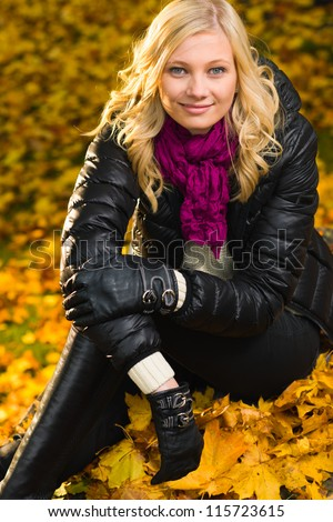 Beautiful girl sitting, autumn color leaves on the background, vertical format - stock photo