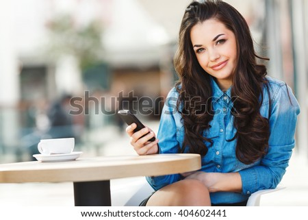 Beautiful girl sitting in cafe in shopping mall, smiling and holding phone with one hand. Head tilted a little bit aside. Coffee on table. Wearing blue jeans blouse, nice make up. Indoor