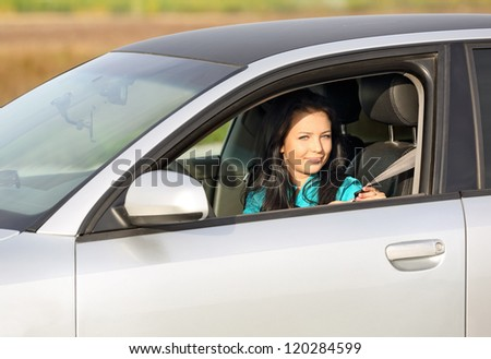beautiful girl sitting in the car and puts on seat belt - stock photo