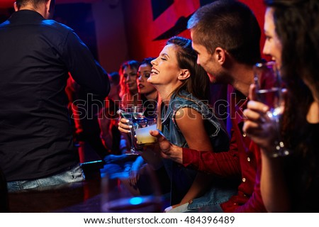 beautiful girl sitting in the club with friends and laughs