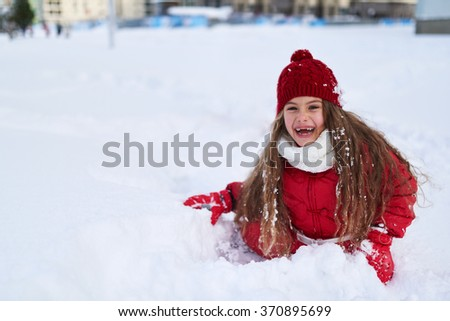 beautiful girl sitting in the snow and laughing with joy