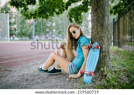 beautiful girl sitting near the skateboard in the park - stock photo