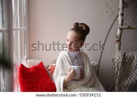 beautiful girl sitting near the window with a cup of tea