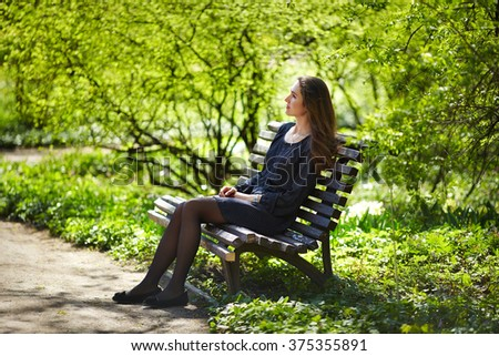 Beautiful girl sitting on a bench in the lush garden. The woman beautiful hair and dreamy look. Spring in the park. - stock photo