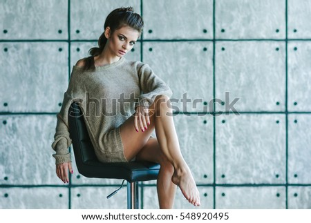 Beautiful girl sitting on a chair. A woman dressed in a soft knit sweater. Photo in a quiet and cozy style. The model have fashionable and stylish hairstyle and make-up.