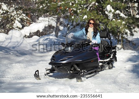 Beautiful girl sitting on a snowmobile in the winter forest - stock photo