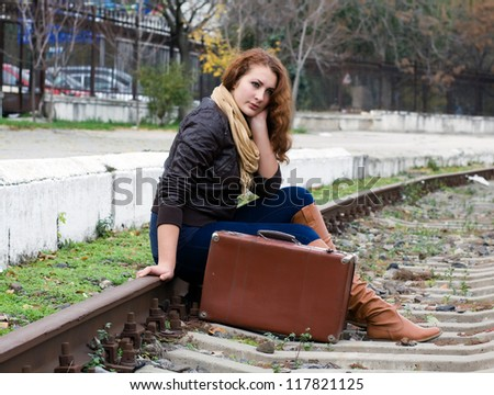Beautiful girl sitting on a suitcase along the train tracks
