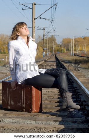 Beautiful girl sitting on a suitcase along the train tracks - stock photo
