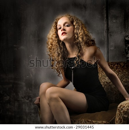 beautiful girl sitting on armchair - stock photo