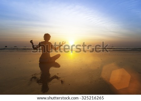 Beautiful girl sitting on beach during sunset and meditating in yoga pose. - stock photo