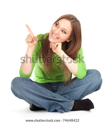 beautiful girl sitting on the floor with crossed legs, pointing up, series - stock photo