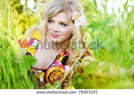 beautiful girl sitting on the grass - stock photo