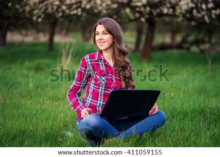 beautiful girl sitting on the grass in the park with laptop