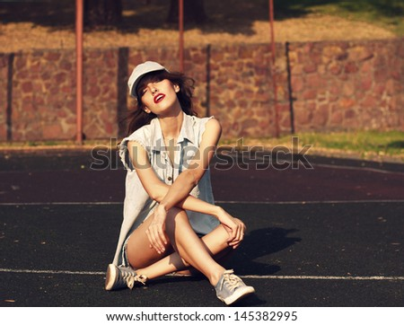 Beautiful girl sitting on the pavement, sunny day, a basketball court.