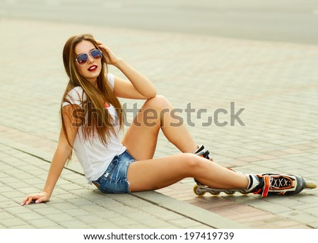 Beautiful girl sitting on the road in roller skates - stock photo