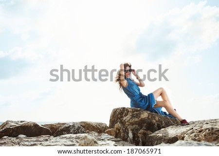 beautiful girl sitting on the rocks in sunglass and blue dress on the sunrise near the sea
