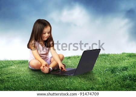 Beautiful girl sitting with a notebook on the lawn - stock photo