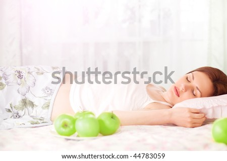 beautiful girl sleeping  in the morning with apples in her bed