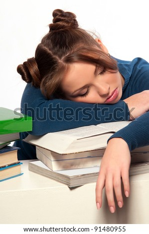 Beautiful girl sleeping on a stack of books, gray background - stock photo