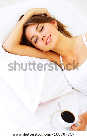 Beautiful girl sleeping on a white bed - stock photo