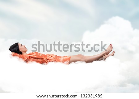 Beautiful girl, sleeping on a white cloud - stock photo