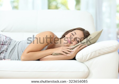 Beautiful girl sleeping or napping happy on a comfortable couch at home - stock photo