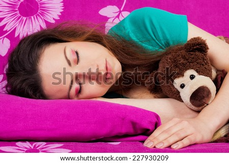 Beautiful girl sleeping with a toy on the bed. Fast asleep young woman brunette with curly unruly hair. - stock photo
