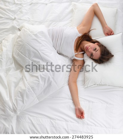 Beautiful girl sleeps in the bedroom, lying on bed .