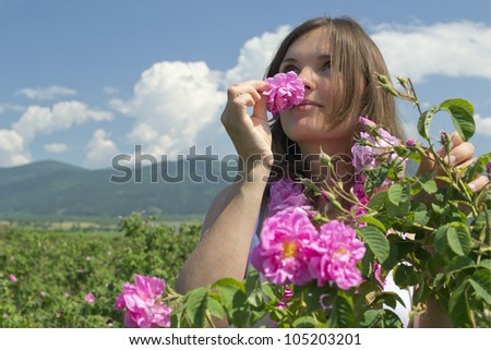 Beautiful girl smelling a rose in a rose field wearing a garland of roses - stock photo
