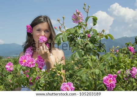 Beautiful girl smelling a rose in rose field wearing a garland of roses - stock photo