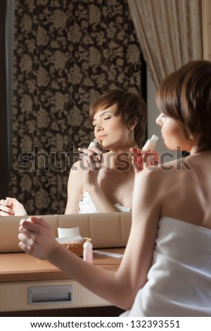 Beautiful girl smelling body lotion - stock photo