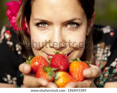 Beautiful girl smelling fresh strawberries in her hand during a picnic in the spring - stock photo