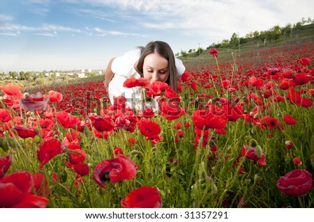 Beautiful girl smelling poppy flowers - stock photo