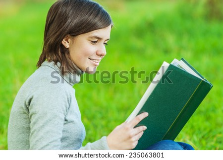 Beautiful girl smiles and looks in book. - stock photo