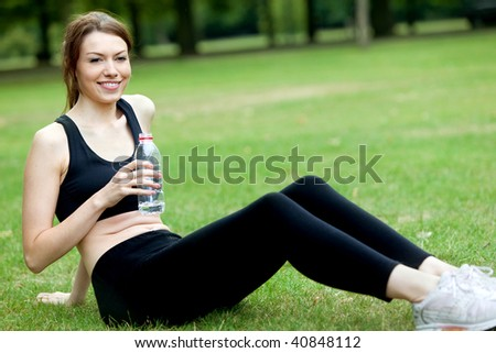 beautiful girl smiling and drinking water after doing abs exercises outdoors - stock photo