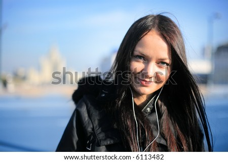 Beautiful girl smiling and  listening portable music outdoors in winter city. Shallow DOF, focus on eyes. - stock photo