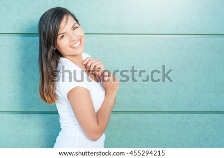Beautiful girl smiling and posing wearing white t-shirt outside on green wall with copy text space - stock photo