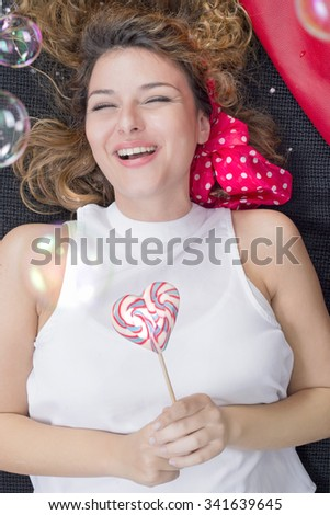 Beautiful girl smiling, lying down and holding a heart shaped lollypop
