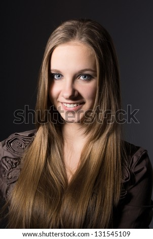 Beautiful girl smiling on gray background - stock photo