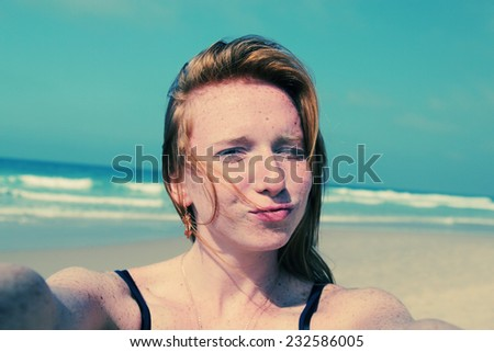 Beautiful girl smiling on the beach with the sand, sea and blue sky in the background. Selfie. - stock photo