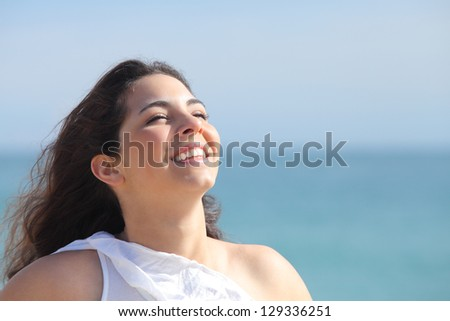 Beautiful girl smiling on the beach with the sea in the background - stock photo