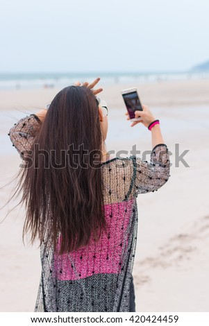 Beautiful girl smiling taking selfie  on the beach with the sand, sea and blue sky in the background. Selfie. - stock photo