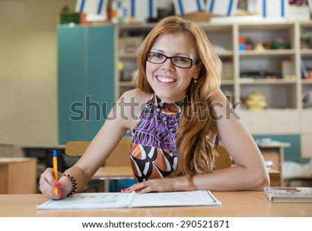 Beautiful girl smiling while sitting at a table and writes - stock photo