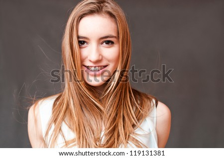 beautiful girl smiling with braces, giving a look - stock photo