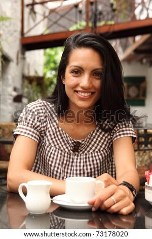 Beautiful girl smiling with coffee in a cafe - stock photo